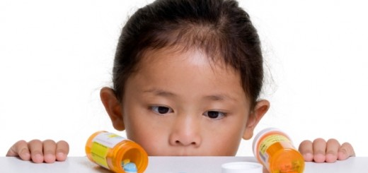Bambina che guarda flaconi con medicinali